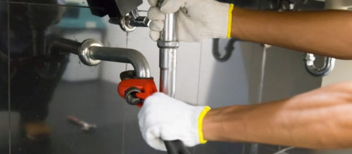 plumber-fixing-white-sink-pipe-with-adjustable-wrench_34936-1945